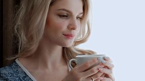A young beautiful blond woman in a blue robe stands by the window of a room and drinks tea or coffee from a white cup. Smiles and gets pleasure stock video footage