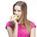 Young beautiful blond woman eating green apple Stock Photo
