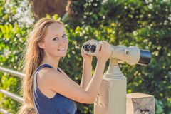 Young beautiful blond woman enjoy the view with an coin operated binoculars. The water and the sky is blue. she wears a white dres royalty free stock image