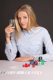 Young beautiful blond woman with glass of champagne playing poke Royalty Free Stock Images