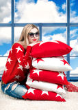 Young beautiful blond woman in glasses from the sun with beautiful pillows. Beautiful,fashionable,original cushions with an orname. Beautiful,fashionable stock photography
