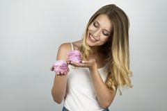 Young beautiful blond woman holding cupcakes in her both hands isolated white background stock photos