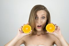 Young beautiful blond woman holding oranges in her hands looking surprised isolated white background royalty free stock photos