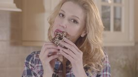 Young beautiful blond woman greedily eating donut and licking her fingers. Young beautiful blond woman with long hair and red lipstick greedily eating donut and stock video