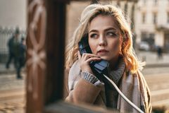 Young beautiful blond woman making an important call in a vintage public phone booth on a sunny evening stock photography