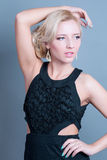Young beautiful blond woman model posing in black dress Royalty Free Stock Image