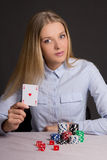 Young beautiful blond woman playing poker over grey Stock Photo