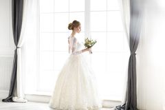 Young beautiful blond woman posing in a wedding dress royalty free stock photography