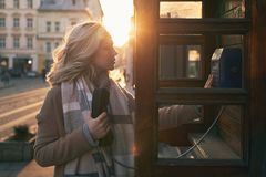 Young beautiful blond woman ready to make an important call in a vintage public phone booth on a sunny evening royalty free stock photos