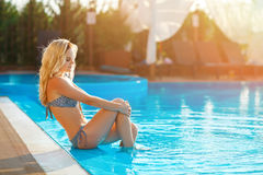 Young beautiful blond woman resting in the swimming pool. stock images