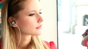 Young beautiful blond woman riding tram, listening to music stock video footage