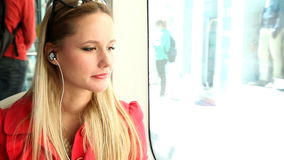 Young beautiful blond woman riding tram, listening to music and dancing stock video footage