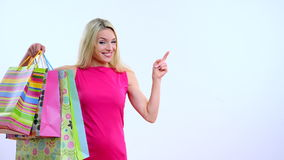 Young beautiful blond woman with shopping bag on the white background.she point out and smiling stock footage