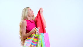Young beautiful blond woman with shopping bag on the white background.she point out and smiling stock video