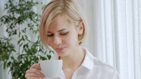 A young beautiful blond woman with short hair with glasses drinks coffee from a white cup in a light apartment. Office life, break, rest and relaxation stock video