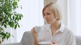 A young beautiful blond woman with short hair with glasses drinks coffee from a white cup in a light apartment. Office life, break, rest and relaxation stock footage