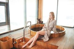 Woman relaxing near wooden barrel bath with glass in spa and sauna concept. Young beautiful blond woman sitting on the edge of wooden tub with a warm water royalty free stock image
