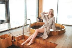Woman relaxing near wooden barrel bath with glass in spa and sauna concept. Young beautiful blond woman sitting on the edge of wooden tub with a warm water stock photos