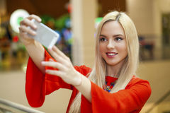 Young beautiful blond woman taking selfie with mobile phone Royalty Free Stock Image