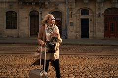 Young beautiful blond woman tourist with a wheeled travel bag and vintage film camera standing on Rynok square in Lviv. Ukraine stock photos