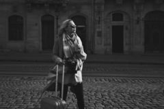 Young beautiful blond woman tourist with a wheeled travel bag and vintage film camera standing on Rynok square in Lviv stock photography
