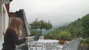 Working on Laptop Outdoors. Young, beautiful blond woman working on laptop and relaxing on terrace with tree, green foliage and misty mountains in the background stock video