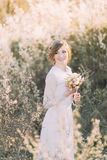 Young beautiful blonde bride wearing white dress with bouquet in blooming meadow. Delicate girl enjoys spring nature Royalty Free Stock Photos