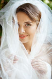 Young beautiful blonde bride in wedding dress and veil smiling. Stock Images