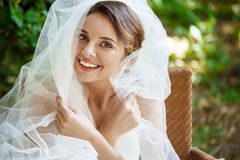 Young beautiful blonde bride in wedding dress and veil smiling. Stock Photos