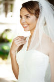 Young beautiful blonde bride in wedding dress and veil smiling. Royalty Free Stock Image