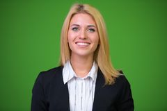 Young beautiful blonde businesswoman against green background stock image