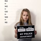 Young beautiful blonde child with a sign covers his face with his hand, Criminal Mug Shots. Young beautiful blonde child with a sign, Criminal Mug Shots stock photography