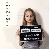 Young beautiful blonde child with a sign, Criminal Mug Shots. difficult children, social tension. Young beautiful blonde child with a sign, Criminal Mug Shots royalty free stock photos