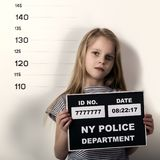 Young beautiful blonde child with a sign, Criminal Mug Shots. difficult children, social tension. Young beautiful blonde child with a sign, Criminal Mug Shots stock photography