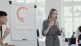 Young beautiful blonde coach business woman speaking before team at modern light office seminar slow motion RED EPIC. Happy female boss leading discussion with stock video footage