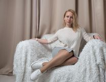 Young beautiful blonde on the couch. An interesting combination of clothes and shoes. Soft tones Stock Images