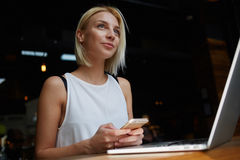 Young beautiful blonde female holding mobile phone while sitting with portable net-book in coffee shop interior, Stock Photo