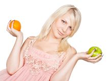 Young beautiful blonde girl and apple and orange Stock Images