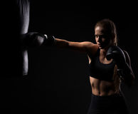 Young beautiful blonde girl in boxing gloves pushes the bag. Beautiful blonde girl in boxing gloves pushes the bag on a black background Stock Image