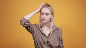 Blonde girl in brown blouse over isolated orange background shows emotions stock footage