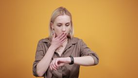 Blonde girl in brown blouse over isolated orange background shows emotions stock video footage