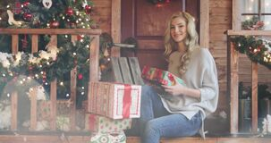 Young beautiful blonde girl with curly hair smiling and giving Christmas gift boxes. Woman in sweater and jeans. New year concept shot on bright background stock video