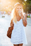 Young beautiful blonde girl drinking coffee from take away cup Royalty Free Stock Photography