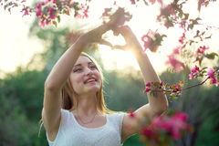 Young beautiful blonde girl holding a heart hands in a flowering sakura garden Royalty Free Stock Image