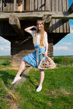 Young beautiful blonde girl with long hair in green field in outdoor ethnic village Pirogovo Royalty Free Stock Photography