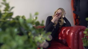 Young beautiful blonde girl making voice message on the phone on the red couch. Domestic plants are in the foreground. Young beautiful blonde girl dials a voice stock video