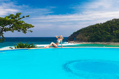 Young beautiful blonde girl is next to the pool. Tropical sea in Royalty Free Stock Photo