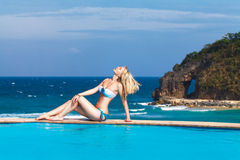 Young beautiful blonde girl is next to the pool. Tropical sea in Royalty Free Stock Image