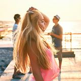 Young beautiful blonde girl in pink top having fun at the evening seaside with her friends on background. Young beautiful blonde girl in pink top having fun at stock photo