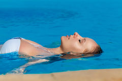Young beautiful blonde girl is in the pool. Summer vacation. Stock Photo